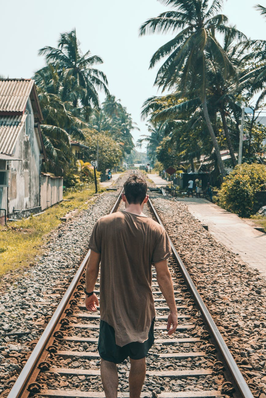 man in brown shirt standing on train rail near coconut palms