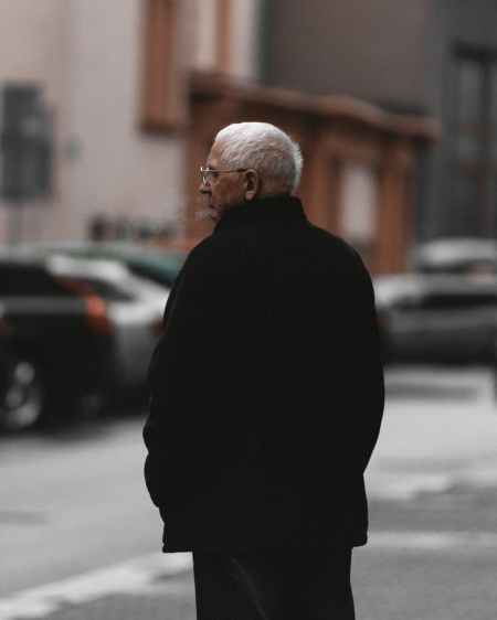 selective focus back view photo of old man in black jacket standing